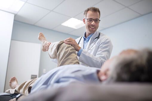Image of a patient laying on a table and a doctor lifting the patient's leg.