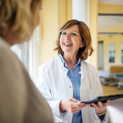 Shot of a smiling senior doctor with a digital tablet talking to a female patient at hospital. Medical professional discussing with woman at nursing home.