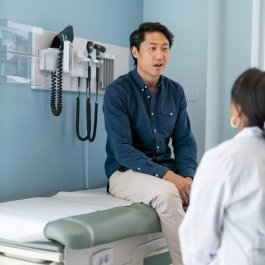 A Korean man is at a routine medical appointment. His doctor is a black woman. The patient is sitting on an examination table facing his doctor.  The kind doctor is listening as he speaks.
