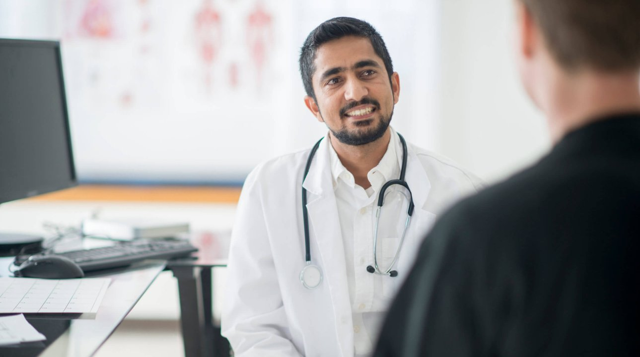 A doctor is sitting and talking with a patient during a check up. He is answering questions about the mans health status.
